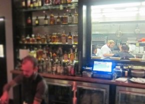 Chef Kris Morningstar seen through the window from the bar at Terrine